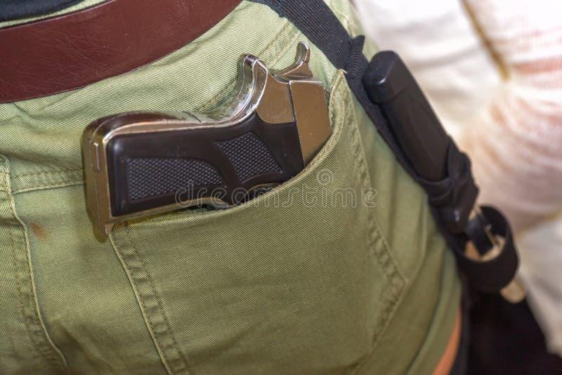 在后面口袋的枪 免版税库存图片
