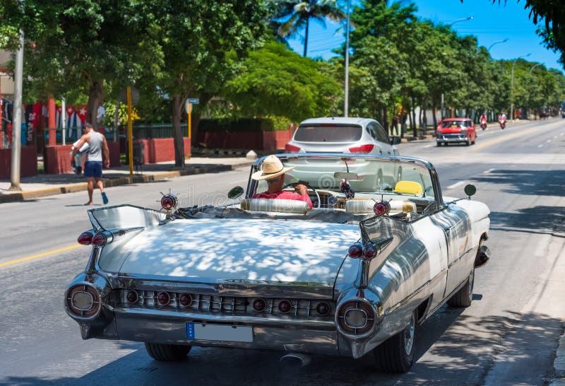 在后面看法的白色经典敞蓬车汽车在有司机的巴拉德罗角古巴 库存照片