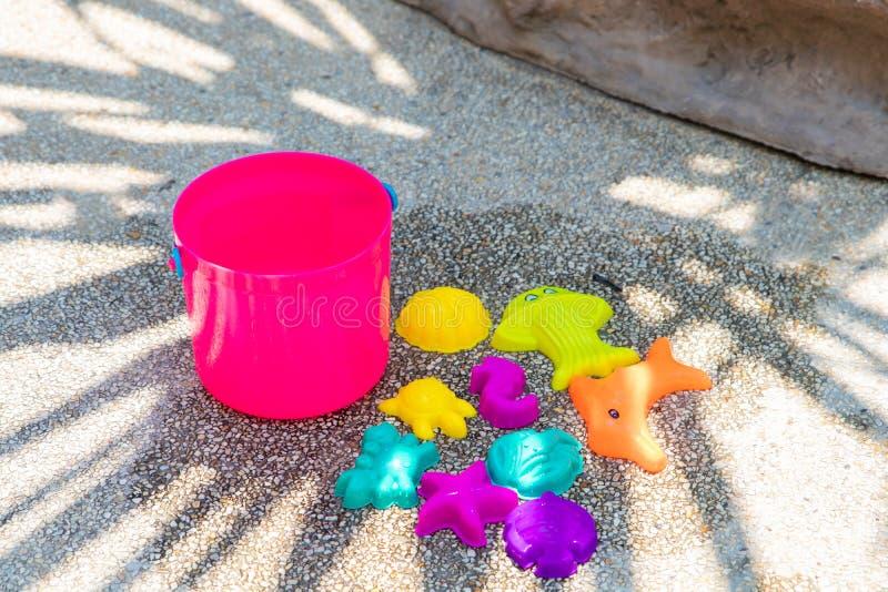 在含沙具体背景的儿童的海滩明亮的桃红色玩具 库存图片