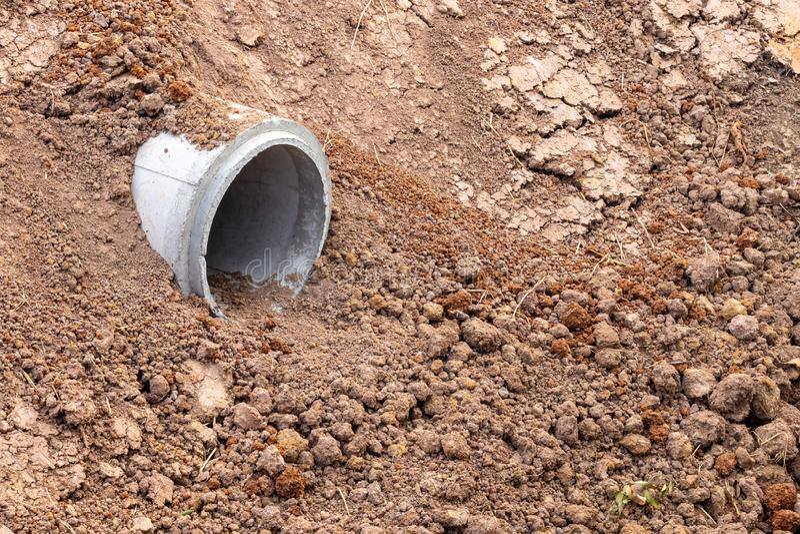 在含沙土壤埋没的小具体管子 免版税库存照片