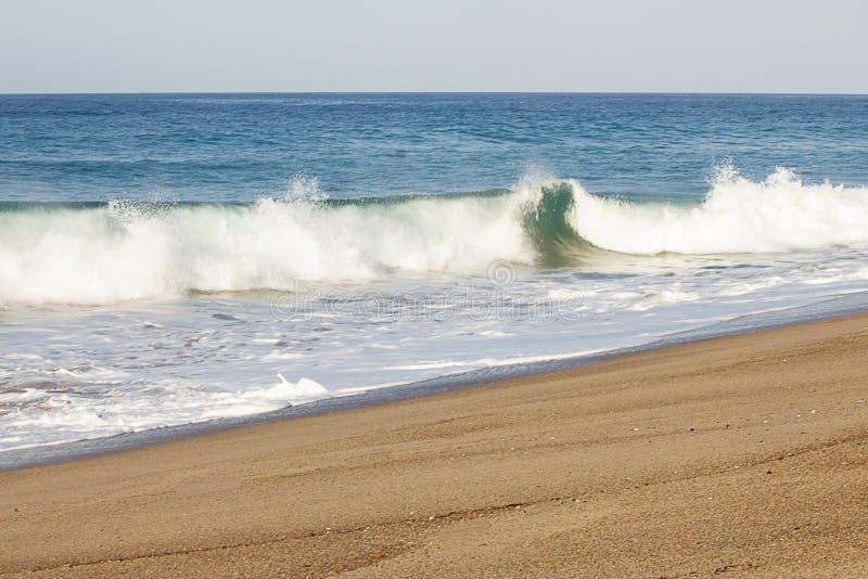 在含沙海岸线的起泡沫的碎波和回流泡沫 免版税图库摄影