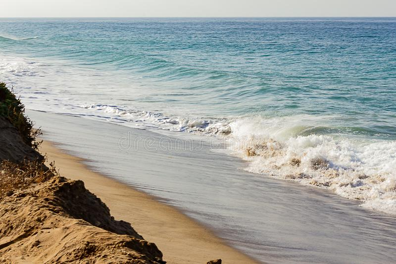 在含沙海岸线的起泡沫的退色的波浪,顶饰的波浪,起泡沫的回流,含沙峭壁上升 免版税库存图片