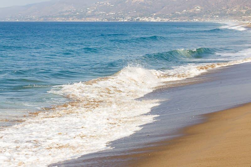 在含沙海岸线的起泡沫的退色的波浪,顶饰的波浪,起泡沫的回流,在海岸线下的顶饰的波浪, 免版税库存图片