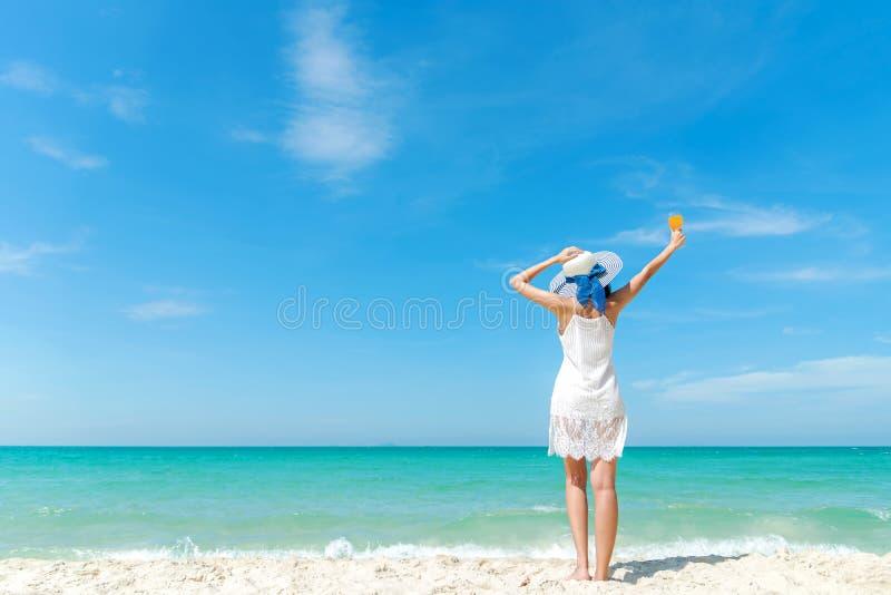 ?? 在含沙海洋海滩的生活方式妇女佩带的白色礼服时尚夏天海滩 愉快的妇女享受和放松vacat 免版税图库摄影