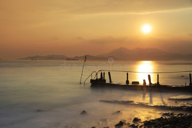 在含沙海湾的剧烈的日落 免版税库存图片