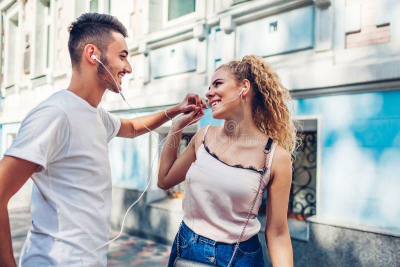 在听到在电话的音乐和跳舞在城市街道上的爱的混合的族种夫妇使用耳机 库存图片