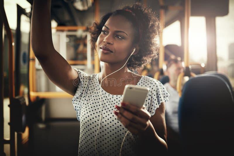 在听到音乐的公共汽车的年轻非洲妇女骑马 免版税图库摄影