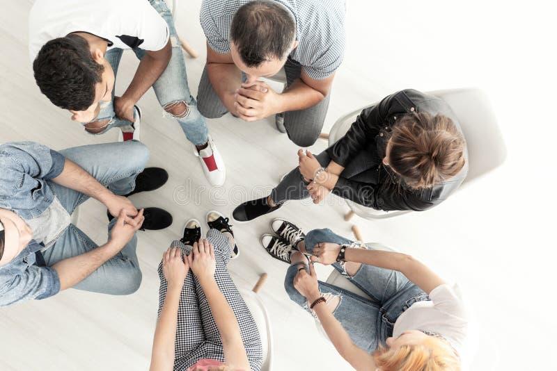 在听心理学家的青年人的顶视图在支持组期间会议  免版税图库摄影