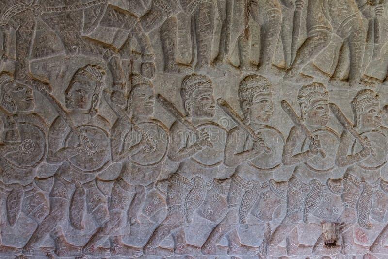 在吴哥窟寺庙,考古学公园,暹粒市,柬埔寨的被雕刻的军事场面 免版税库存图片