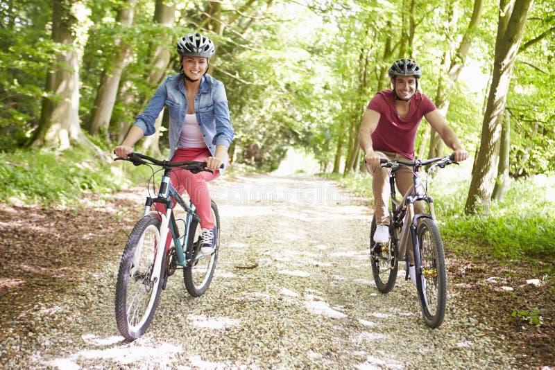 在周期乘驾的年轻夫妇在乡下 图库摄影