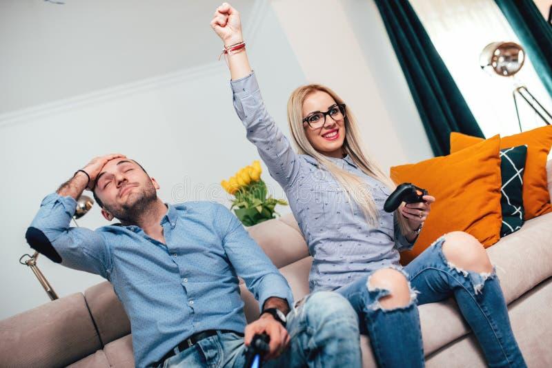在周末,业余时间细节结合获得乐趣 享用电子游戏和女孩的夫妇赢取 免版税图库摄影