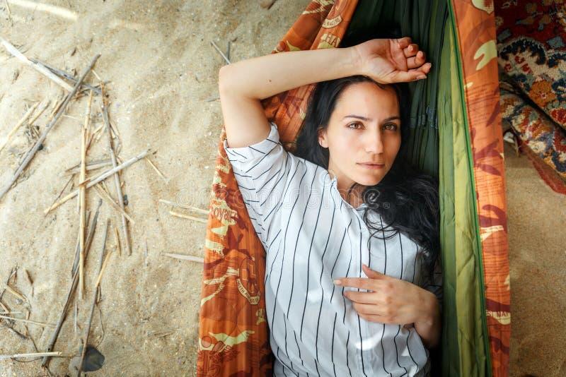 在和放松在沙滩的一个吊床和享受休息,一名成功的自由的妇女的画象的可爱的年轻女人 免版税库存照片