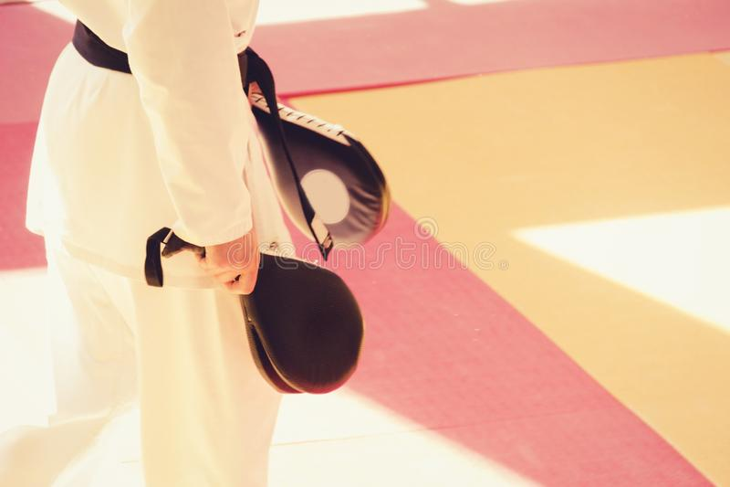 在和服的空手道教练员有一个踢的目标垫的在他的手上在训练期间的健身房 免版税库存照片