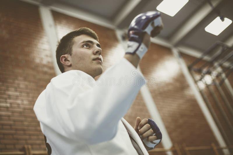 在和服的年轻男性实践的柔道有战斗手套的 免版税库存照片