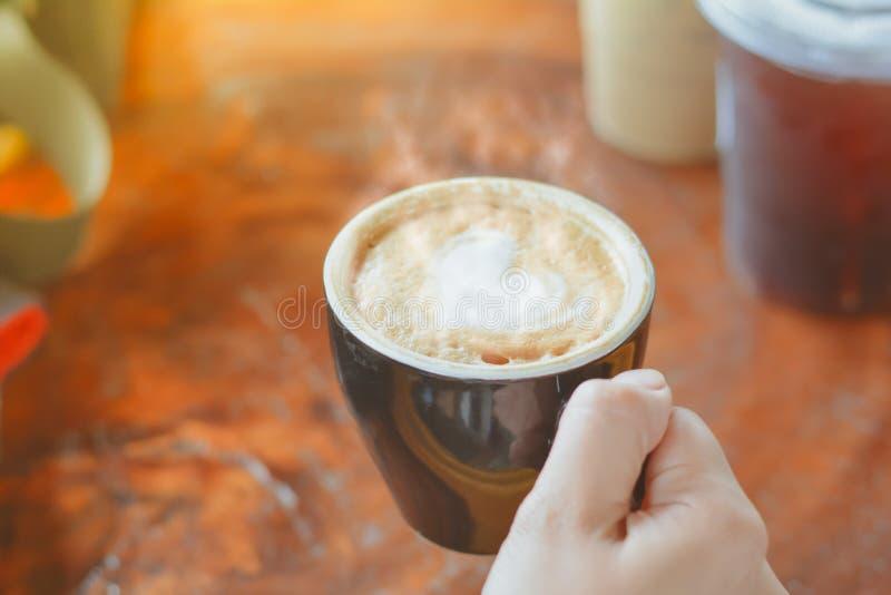 在咖啡店和咖啡厅,手拿黑色陶瓷杯,把热咖啡、配着牛奶拿铁的心形咖啡和复古色调的咖啡 库存照片