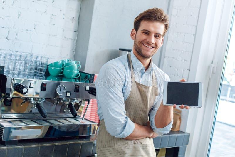 在咖啡店工作的年轻成咖啡师展示有复制空间的平板电脑 库存照片