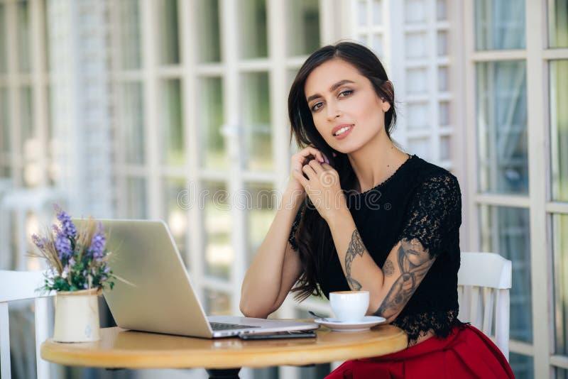 在咖啡店用笔记本电脑工作的美女商人,女自由职业者 免版税库存照片
