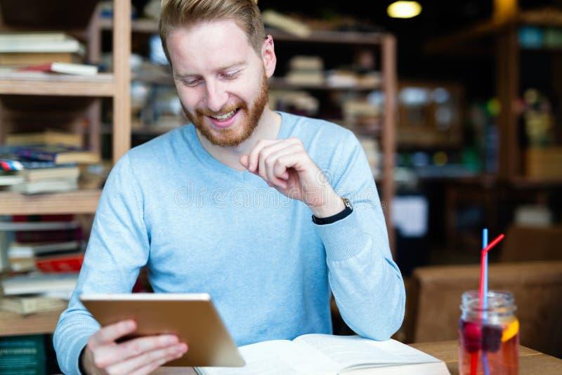 在咖啡店的年轻男学生读书 免版税库存图片