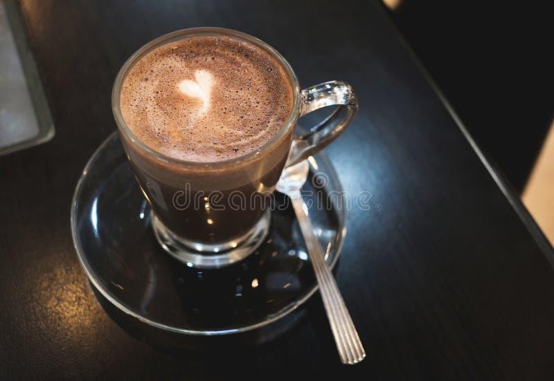 在咖啡杯的布朗可可粉有在黑木桌背景的白色心脏形状的 免版税库存照片