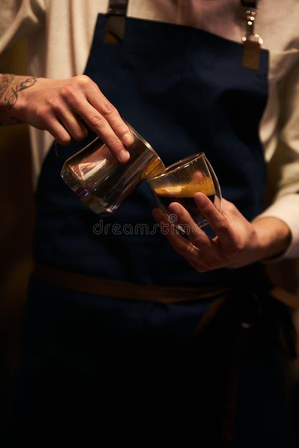 在咖啡杯的Barista倾吐的牛奶为做拿铁艺术 免版税库存图片