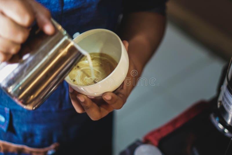 在咖啡杯的Barista服务的牛奶 免版税库存照片