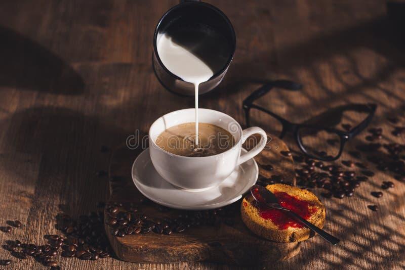 在咖啡杯里加牛奶 库存照片