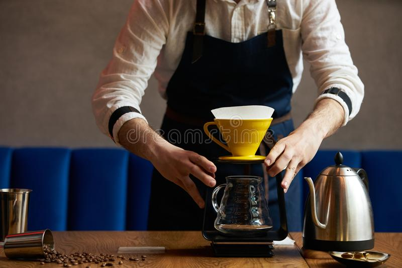 在咖啡渣的Barista倾吐的水与纸过滤器 库存照片
