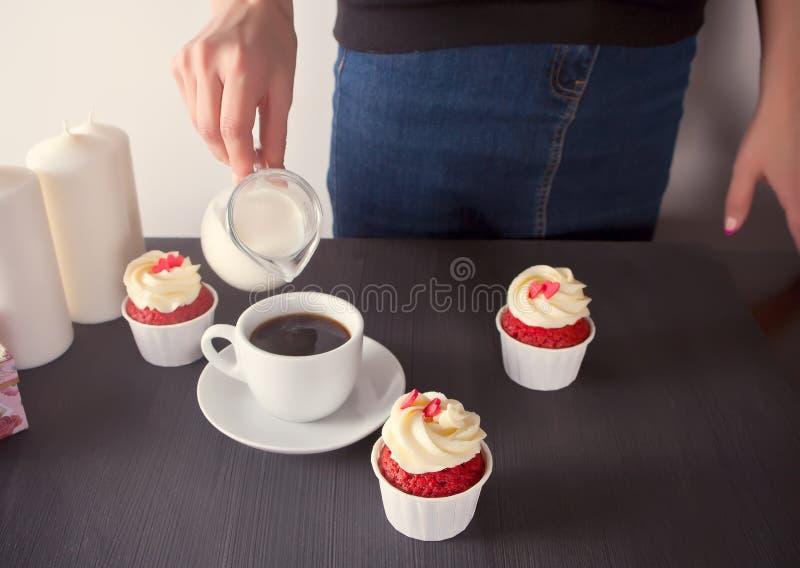 在咖啡的妇女倾吐的牛奶 与可口奶油的三块杯形蛋糕与心脏 免版税图库摄影