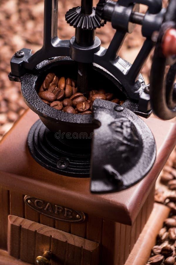 在咖啡粒被弄脏的背景的减速火箭的磨咖啡器  特写镜头 免版税图库摄影