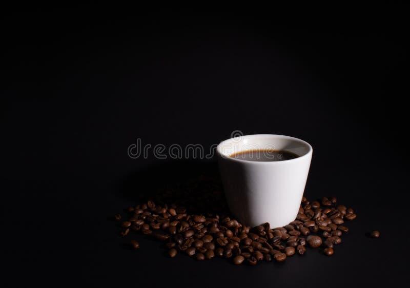 在咖啡粒设置的一个白色杯子的侧灯 免版税图库摄影