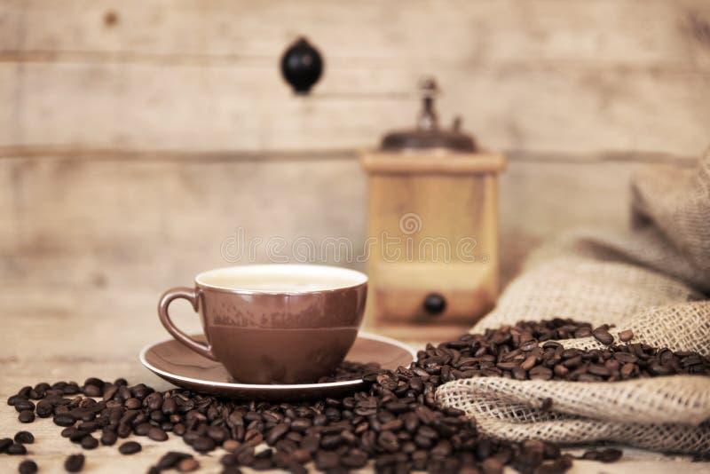 在咖啡豆、杯子和磨咖啡器的老年迈的静物画 库存图片