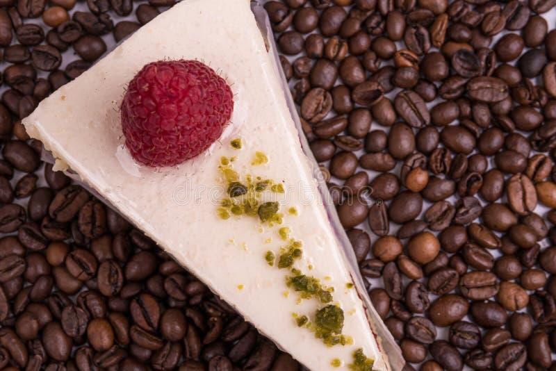 在咖啡豆背景的乳酪蛋糕 免版税库存照片