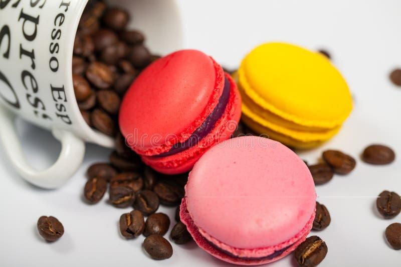 在咖啡豆,杯子的五颜六色的法国可口蛋白杏仁饼干用在白色背景关闭的咖啡豆 库存图片