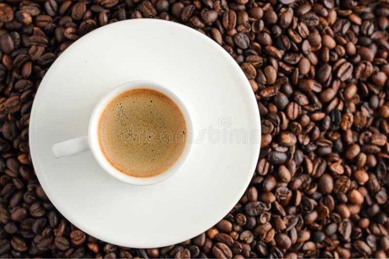 在咖啡豆backgroun的咖啡杯浓咖啡 顶视图 库存图片