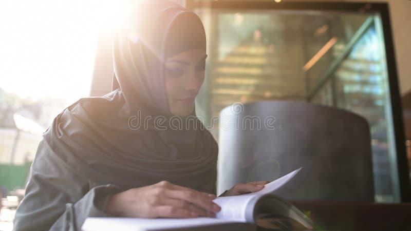 在咖啡馆、教育和自我发展的自信阿拉伯夫人看书 库存照片