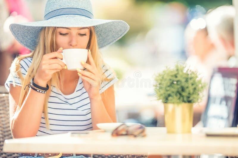 在咖啡馆大阳台的美女饮用的咖啡 夏天画象年轻女人 免版税库存图片