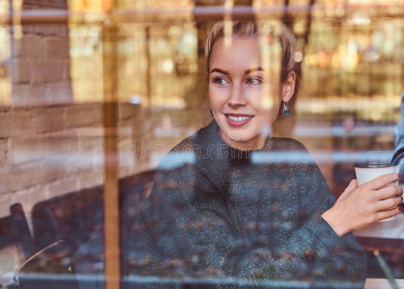 在咖啡馆的一份美丽的微笑的女孩饮用的咖啡 免版税库存照片