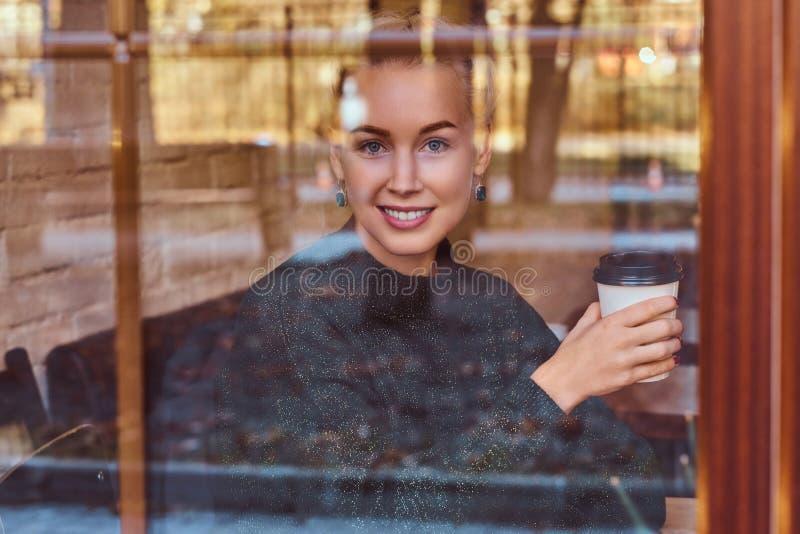 在咖啡馆的一份美丽的微笑的女孩饮用的咖啡 免版税库存图片