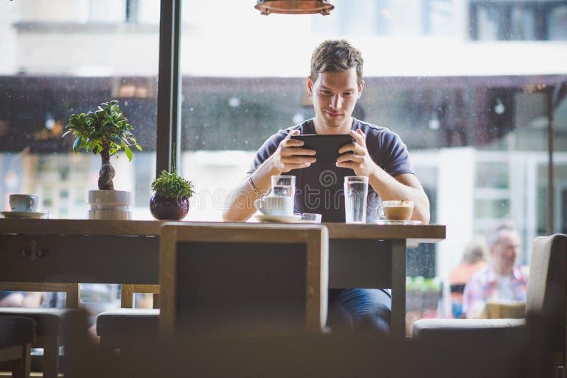 年轻在咖啡馆的人观看的片剂 免版税库存照片
