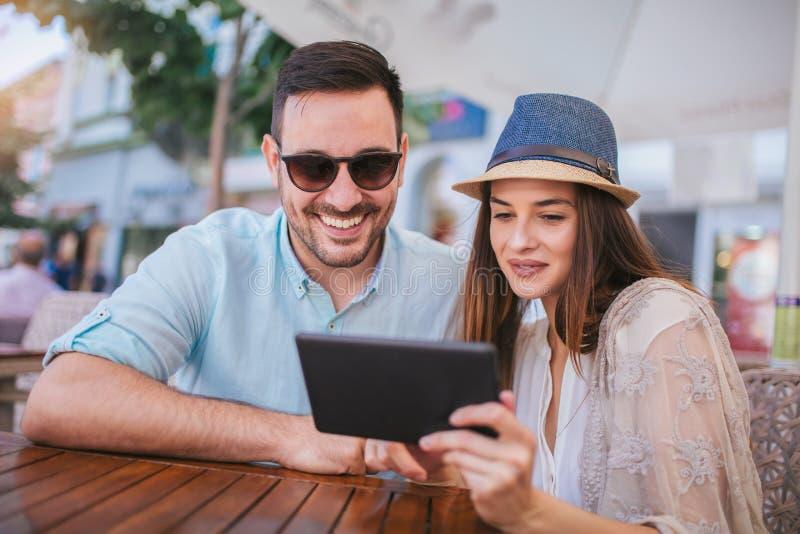 在咖啡馆的可爱的夫妇使用数字式片剂 库存照片