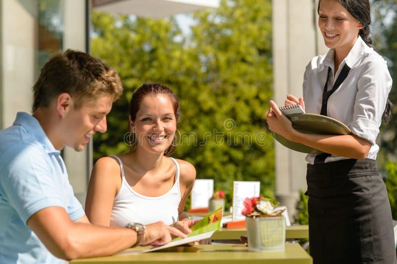 在咖啡馆的夫妇预定从菜单女服务员 库存照片