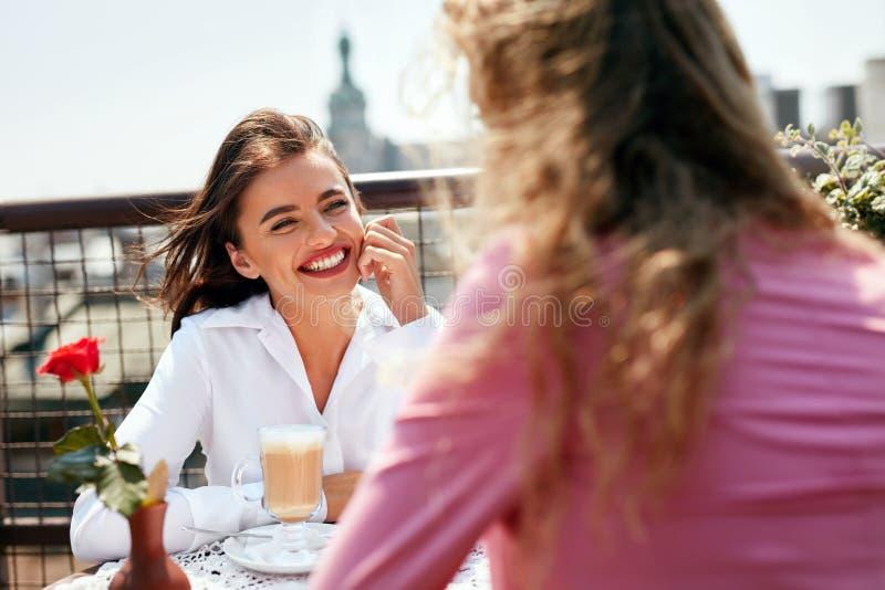 在咖啡馆的妇女饮用的咖啡与朋友户外 图库摄影