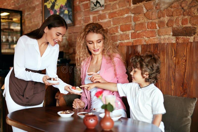 在咖啡馆的家庭 女服务员服务巧克力照顾的和儿子 库存图片