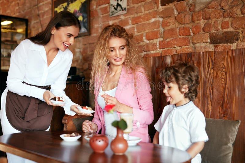 在咖啡馆的家庭 女服务员服务巧克力照顾的和儿子 免版税图库摄影