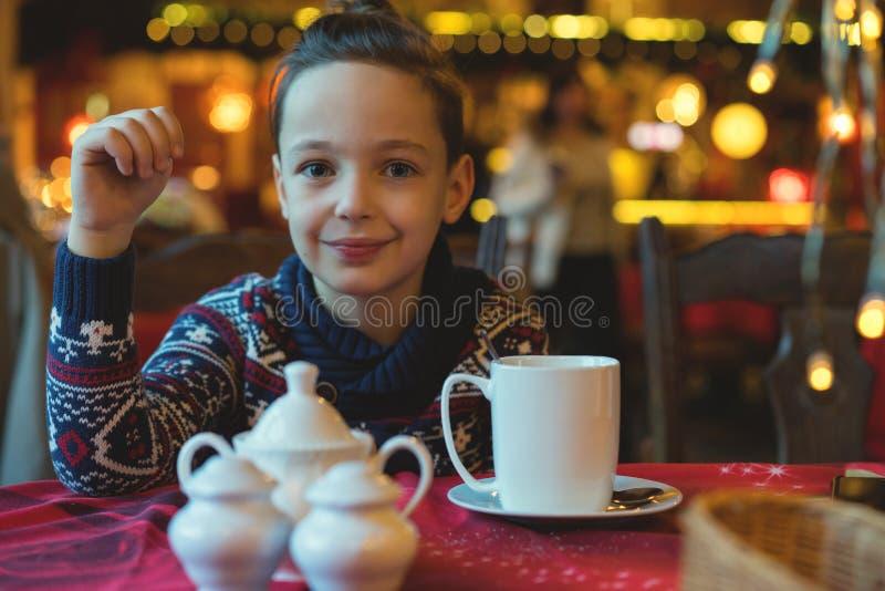 8在咖啡馆的年男孩饮用的茶与圣诞灯 免版税库存照片