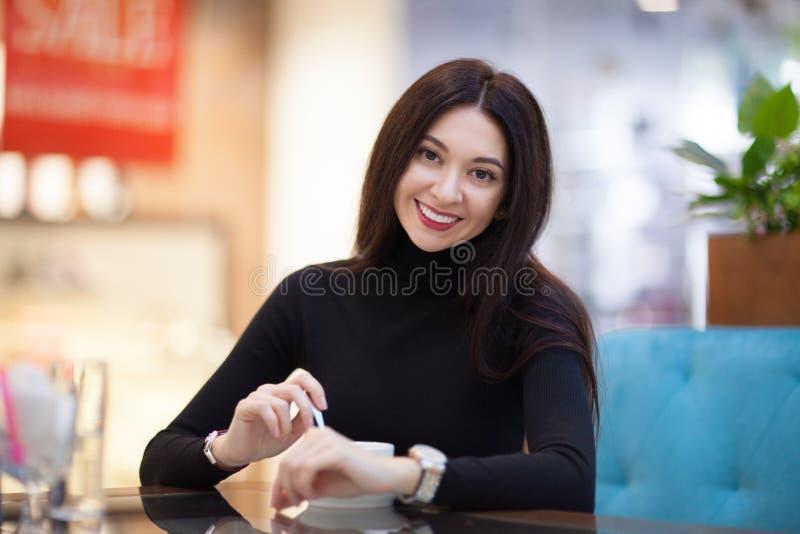 在咖啡馆的微笑的妇女饮用的咖啡 美丽的愉快的时髦的妇女画象  时尚生活方式 库存图片