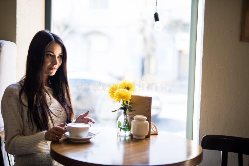在咖啡馆的微笑的年轻女人饮用的咖啡和看窗口 免版税库存图片