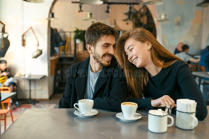在咖啡馆的挥动的年轻夫妇 免版税库存照片