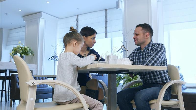 在咖啡馆的母亲、父亲和女儿饮用的茶 父母有一次讨论在电话以后 免版税库存图片