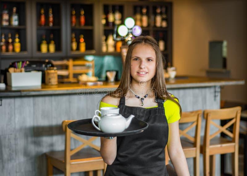 在咖啡馆的画象年轻女服务员身分 女孩侍者在束拿着有器物的一个盘子 库存照片